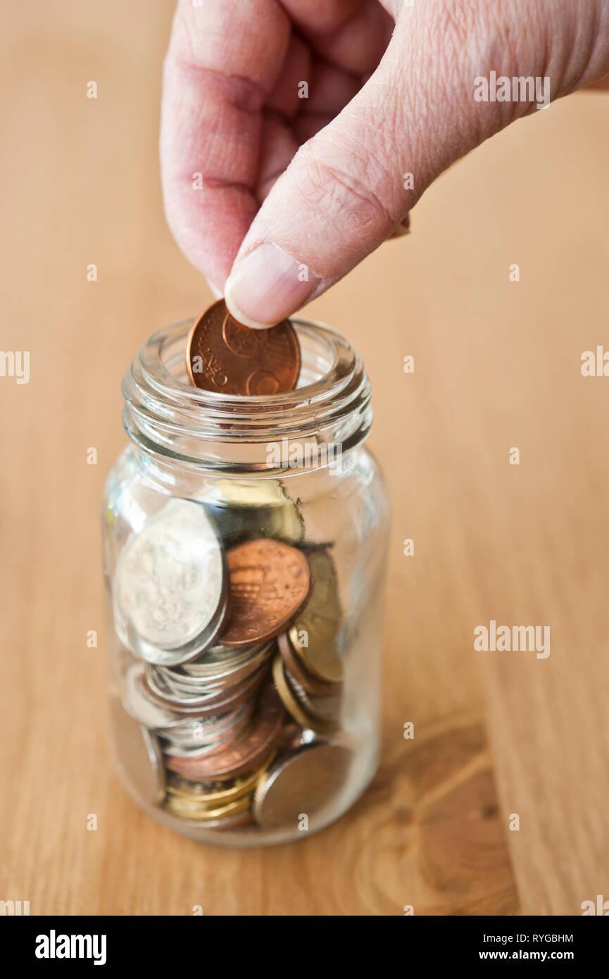 hand putting a coin into a saving jar - Stock Image