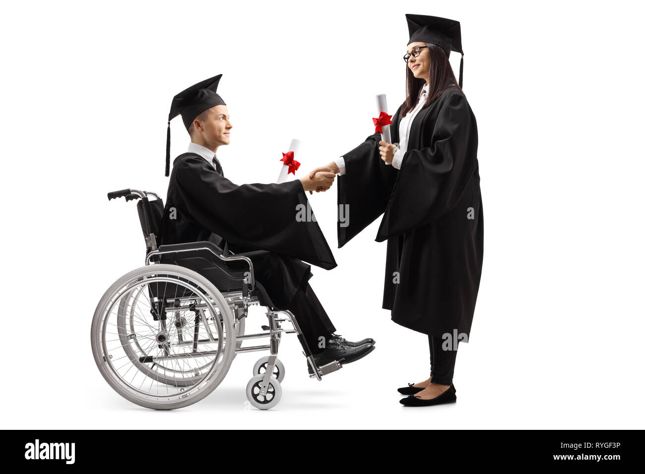 Full length shot of a male graduate student in a wheelchair shaking hand with a female graduate student isolated on white background - Stock Image