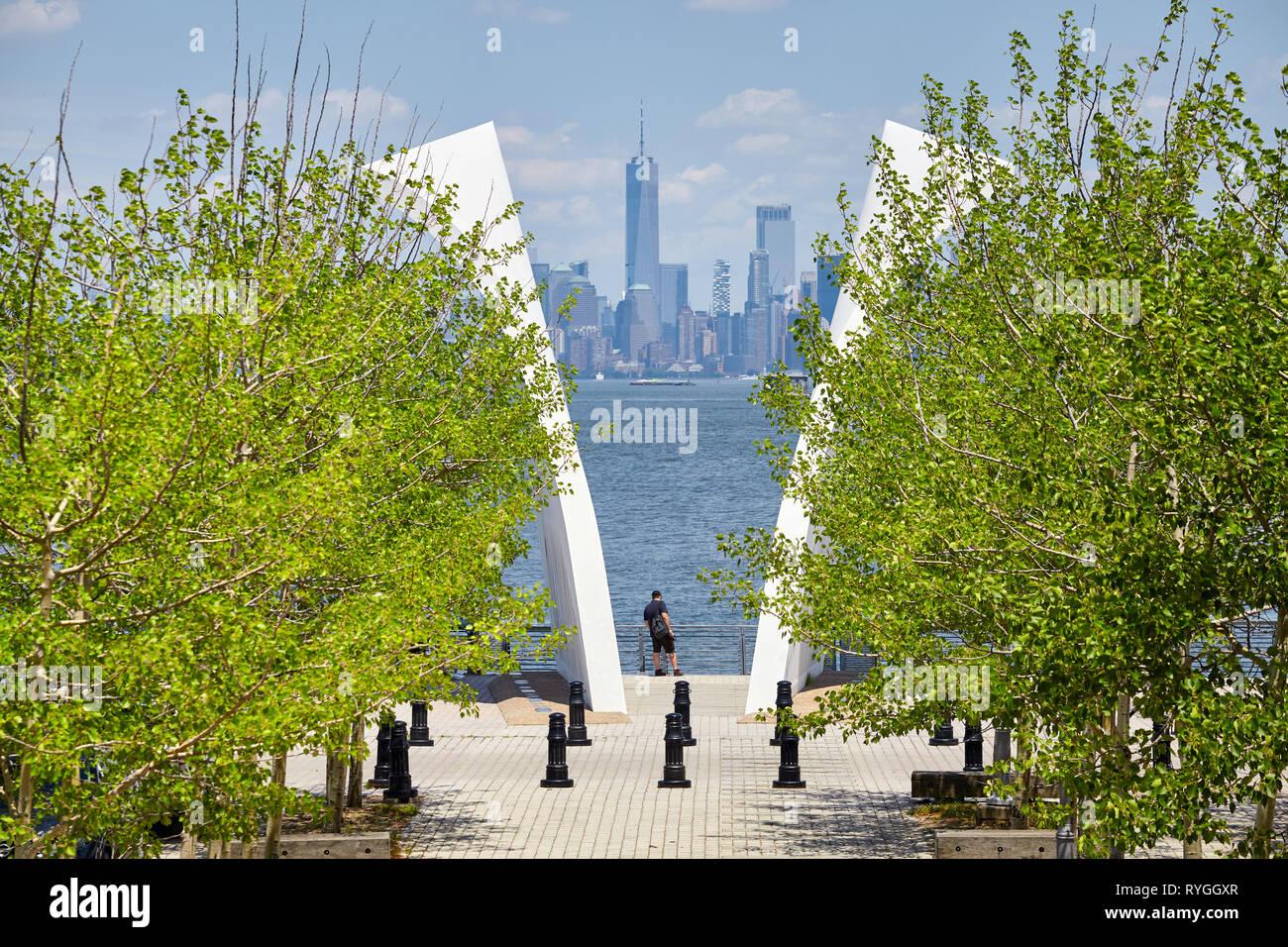 New York, USA - June 29, 2018: Man stands between Postcards, Staten Island September 11 Memorial with Manhattan in distance. Stock Photo