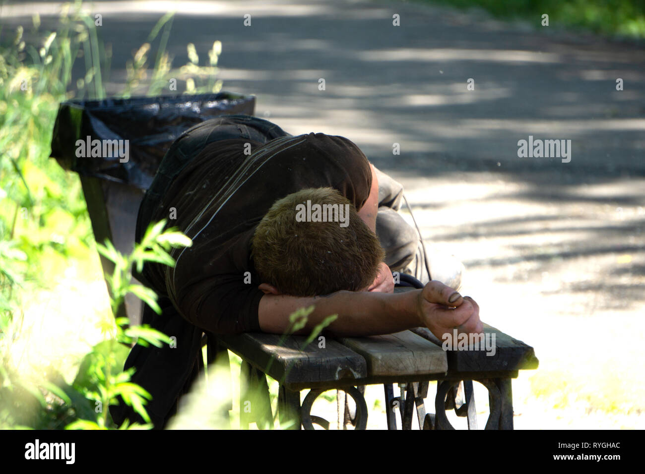 Drunk man sleeping in park on wooden bench - Stock Image