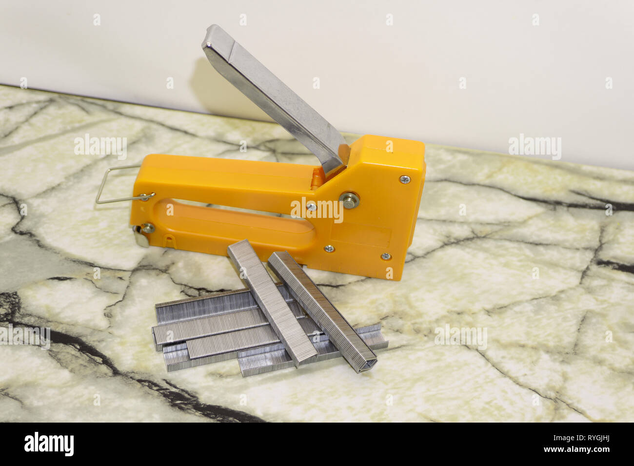 Large stapler and staples for construction work on white - Stock Image
