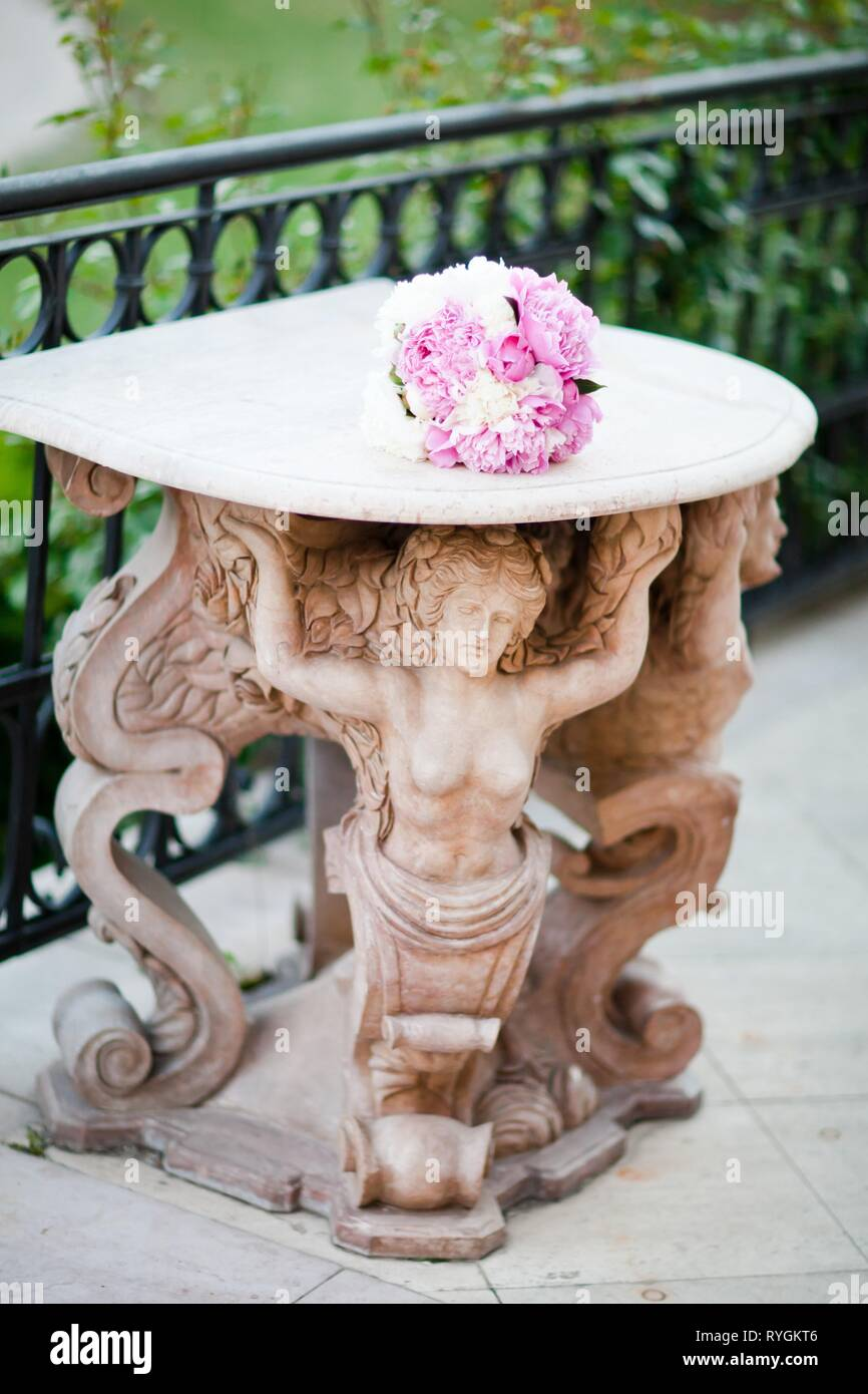 Antique statue supporting a table with wedding bouquet. Simple purple-white colored flowers. - Stock Image