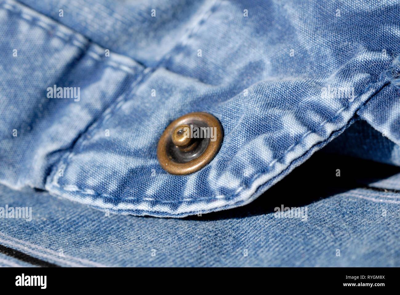 Button closure on a blue denim shirt closeup. Shallow depth of field - Stock Image