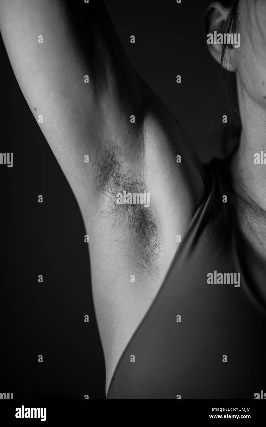 Close-up, portrait, front view of Caucasian woman with hairy armpits. Black and white close up of attractive female unshaven armpit. - Stock Image