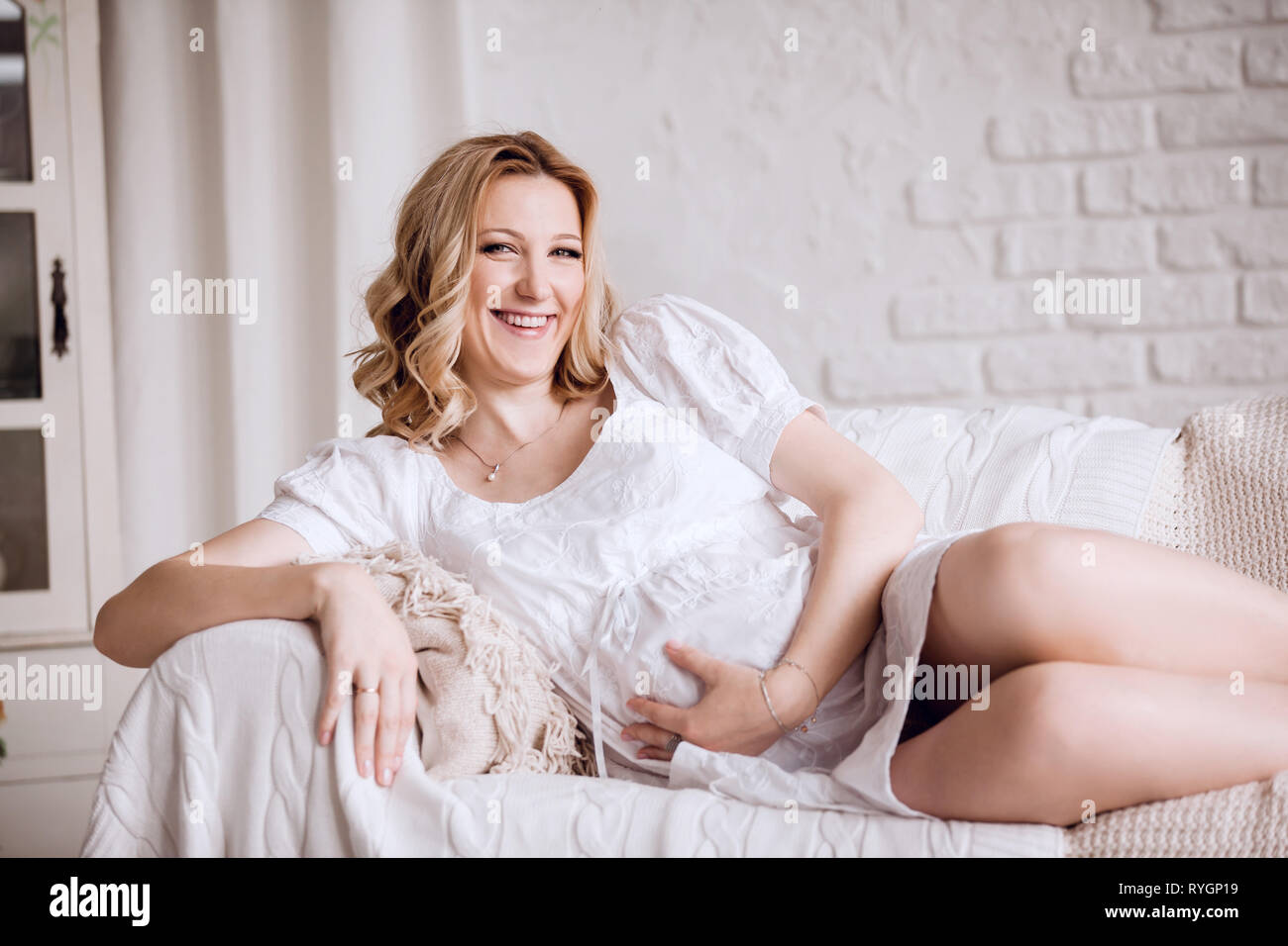 close up. young pregnant woman lying on couch - Stock Image