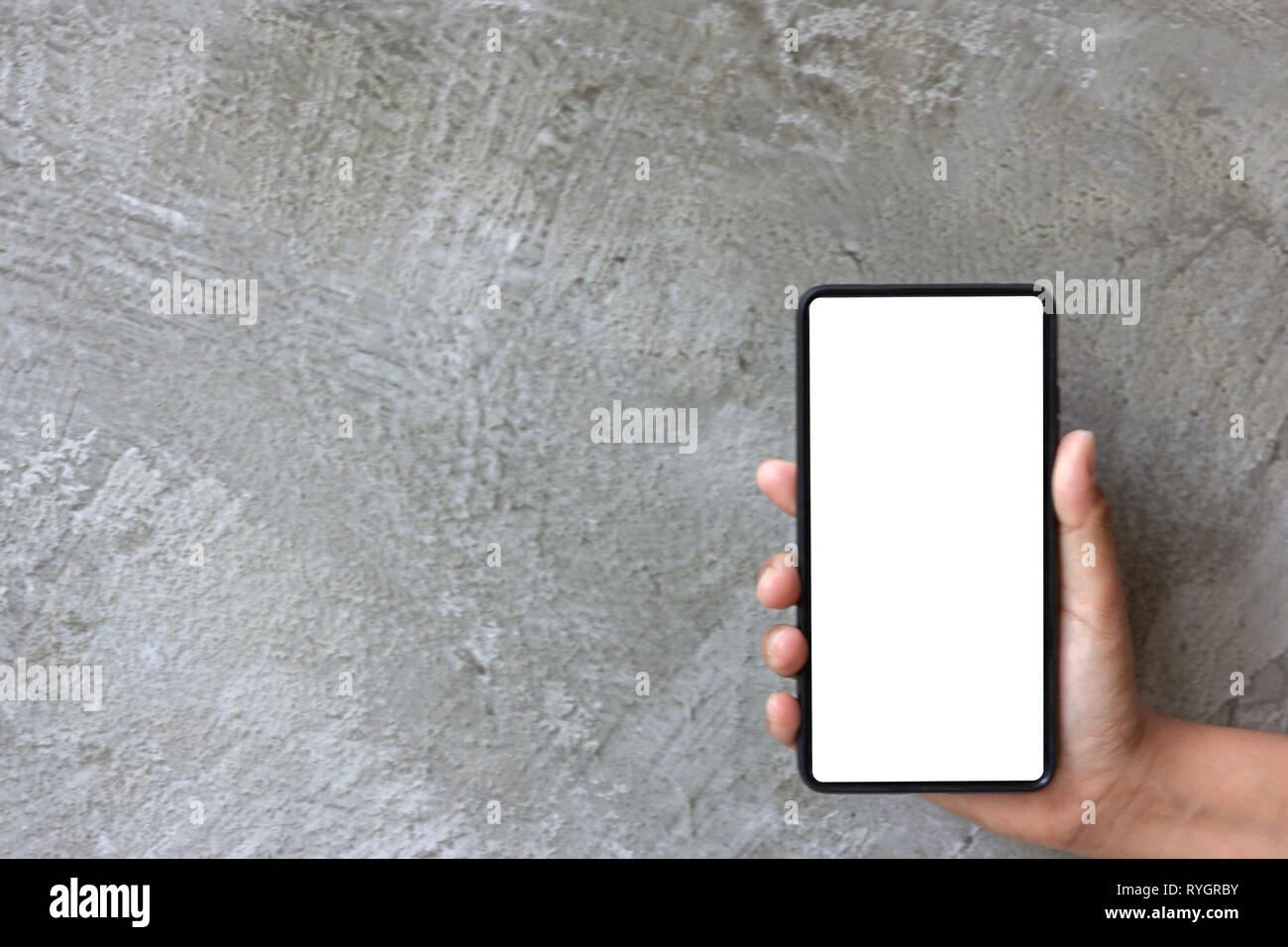 Asian woman hand hold moblie phone on grey cement background Stock Photo
