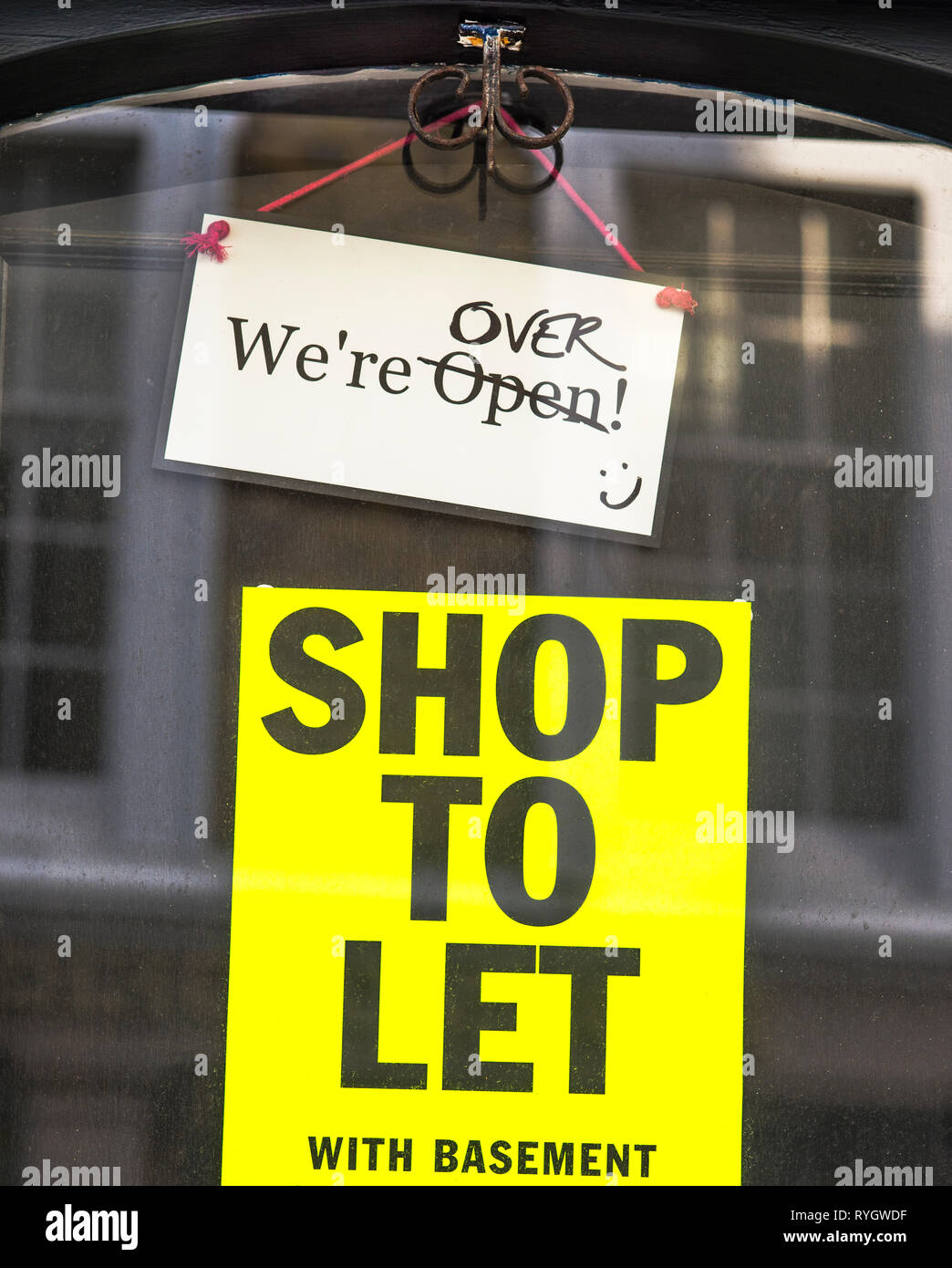 Signage on shop door announcing shop is closing and premises are for let - Stock Image