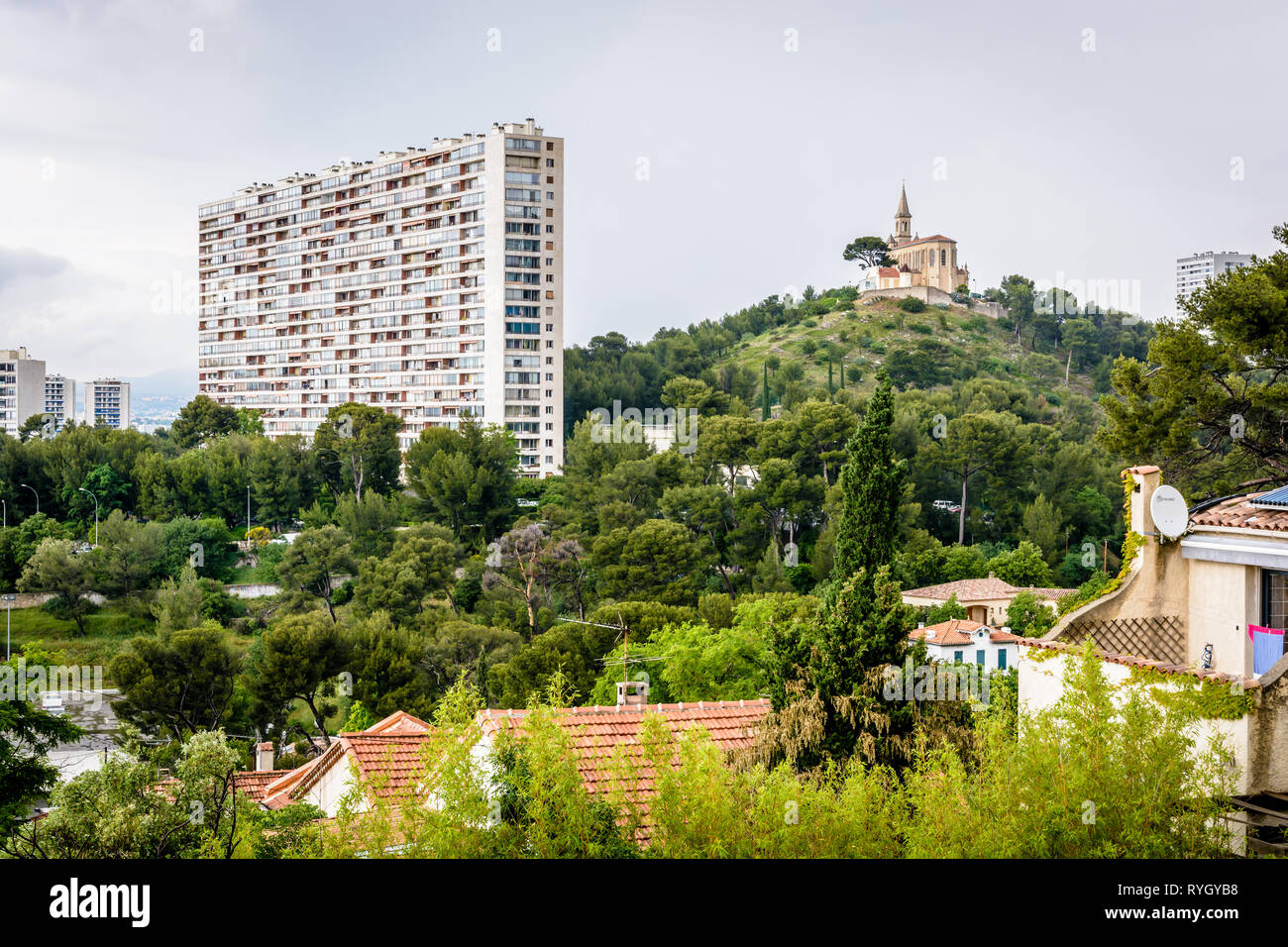 Saint-Joseph du Cabot chapel on Saint-Joseph hilltop in Le Cabot district and one of the residential buildings of the Residence Valmante in Marseille. - Stock Image