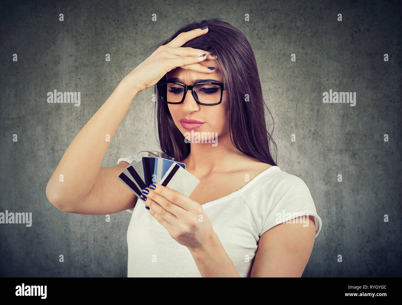 Confused stressed woman looking at too many credit cards full of debt - Stock Image