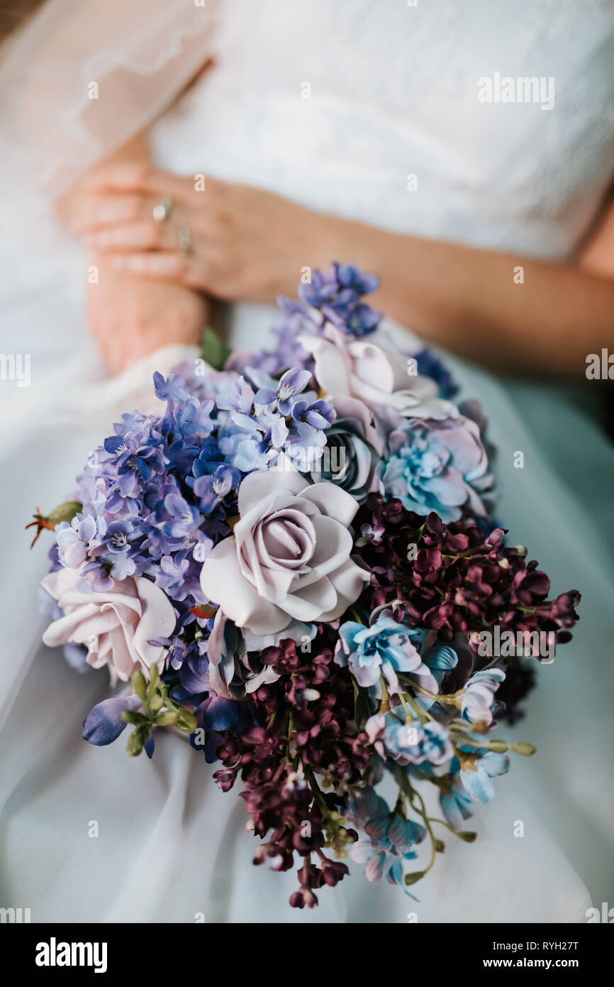 Bride Holding The Wedding Bouquet With Blue And Violet Flowers On