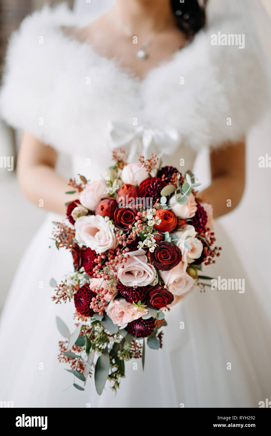 Red And White Wedding.Bride Holding The Wedding Bouquet With Pink And Red Flowers On White
