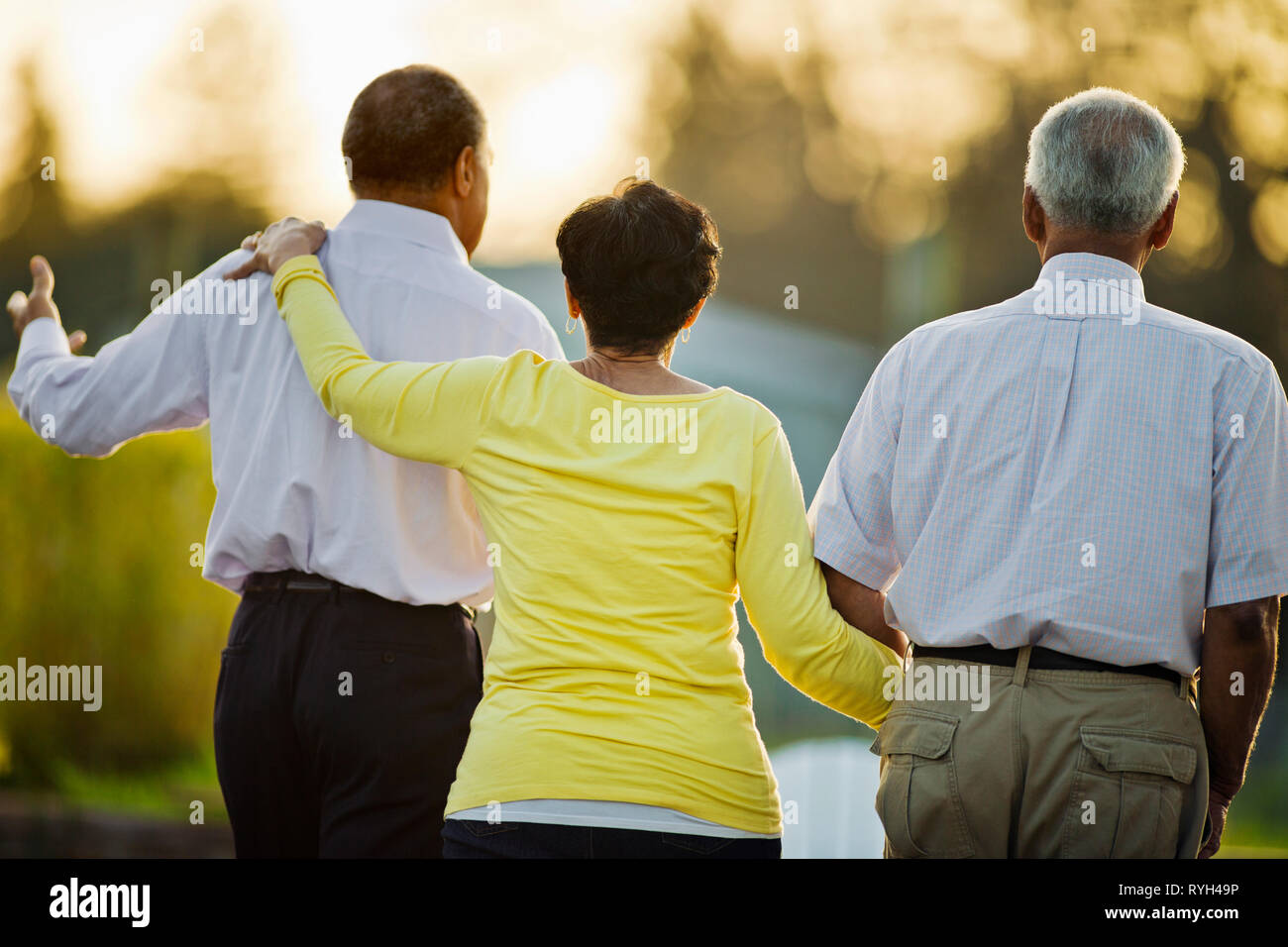 Happy group of senior adults walking together in the back yard. - Stock Image
