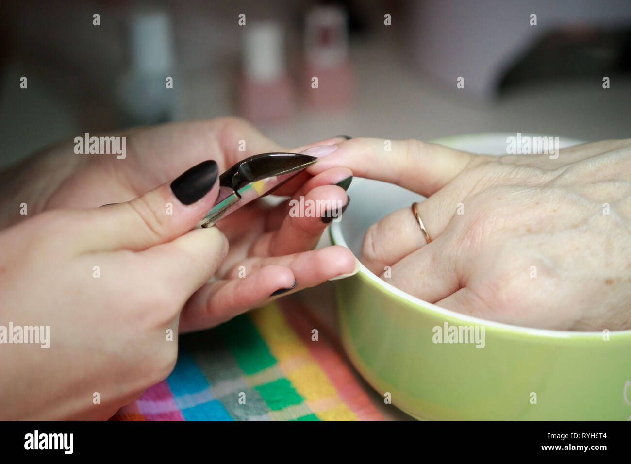 nail service manicurist makes an elderly woman manicure with a metal tool - nippers. Moving off the nail cuticle. reporting shooting Stock Photo