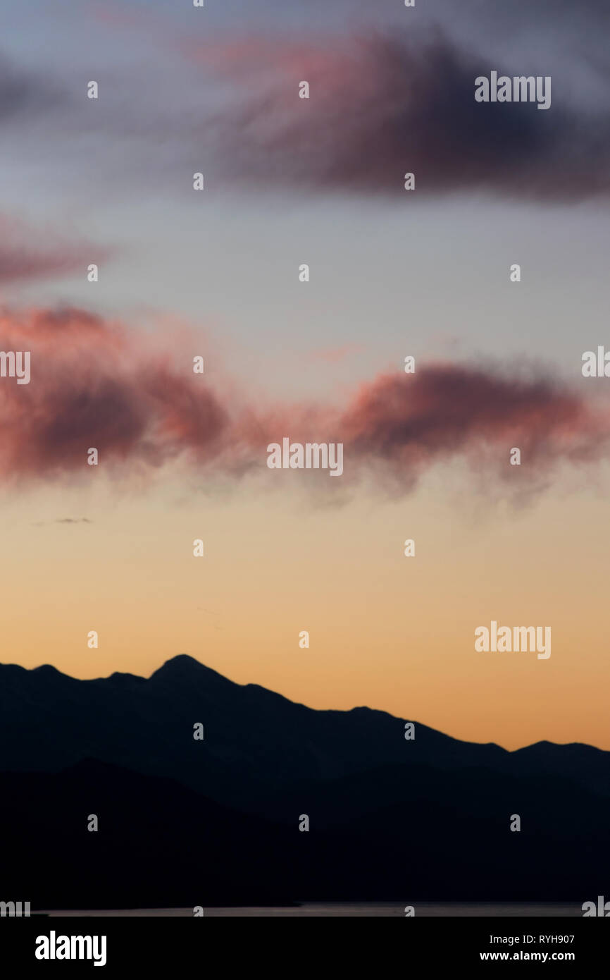 Tranquillity view  romantic sunset sky against mountain silhouette - Stock Image
