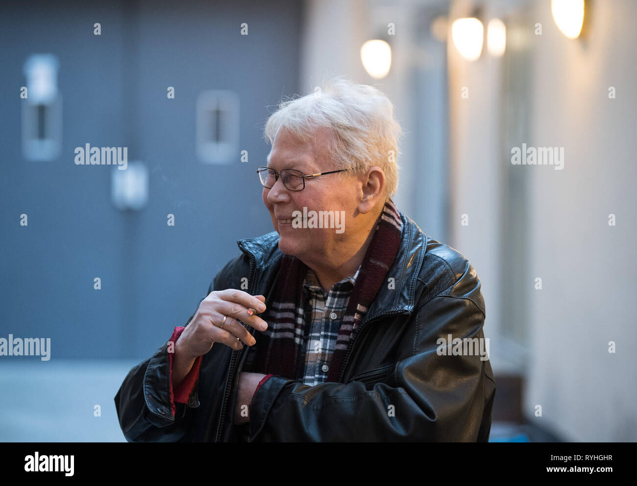 Berlin, Germany. 13th Mar, 2019. Director Harry Kupfer smokes during the break of the photo rehearsal of Handel's opera 'Poros' in a courtyard of the Komische Oper. Premiere of the piece is on 16.03.2019. Credit: Soeren Stache/dpa/Alamy Live News - Stock Image
