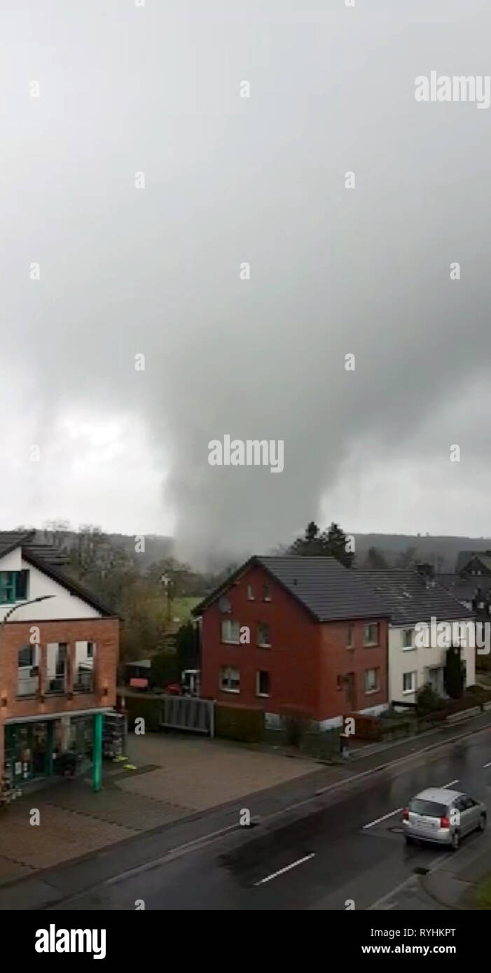Roetgen, Germany. 14th Mar, 2019. A tornado moves over Roetgen. A tornado in the Eifel municipality of Roetgen has covered roofs, damaged houses and frightened the inhabitants. The storm center hit the main street of the village, several houses can no longer be inhabited for the time being. Credit: Tnn/TeleNewsNetwork/dpa/Alamy Live News - Stock Image