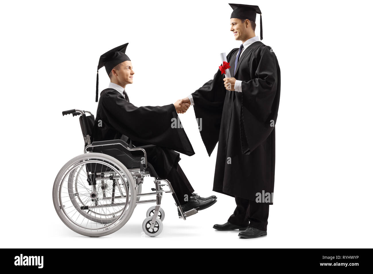 Full length shot of a male graduate student in a wheelchair shaking hand with a male graduate student standing and holding a diploma isolated on white - Stock Image