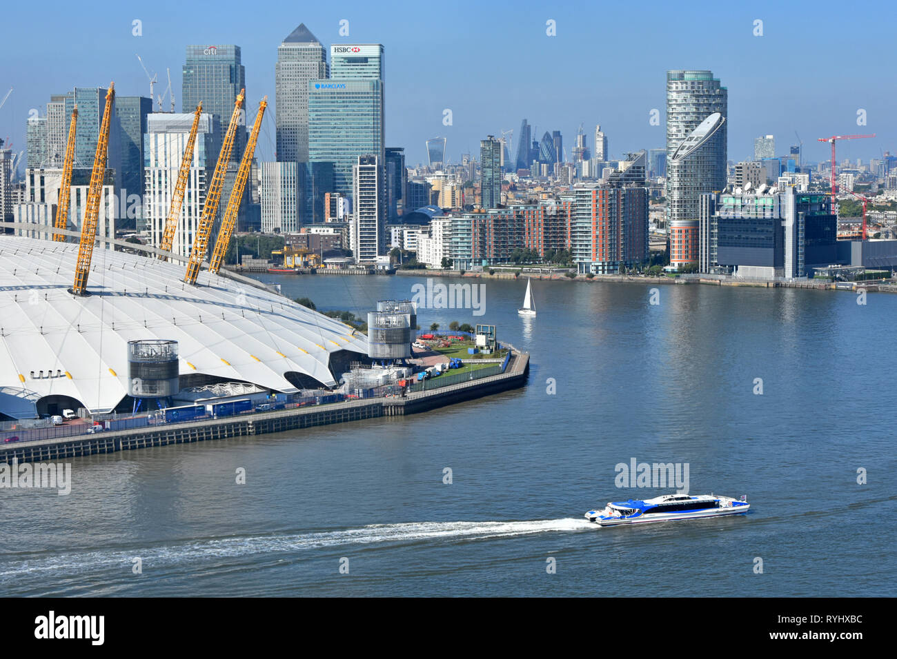Aerial view looking down from above at bend in River Thames with clipper boat & London Canary Wharf cityscape skyline o2 arena dome roof Greenwich UK - Stock Image