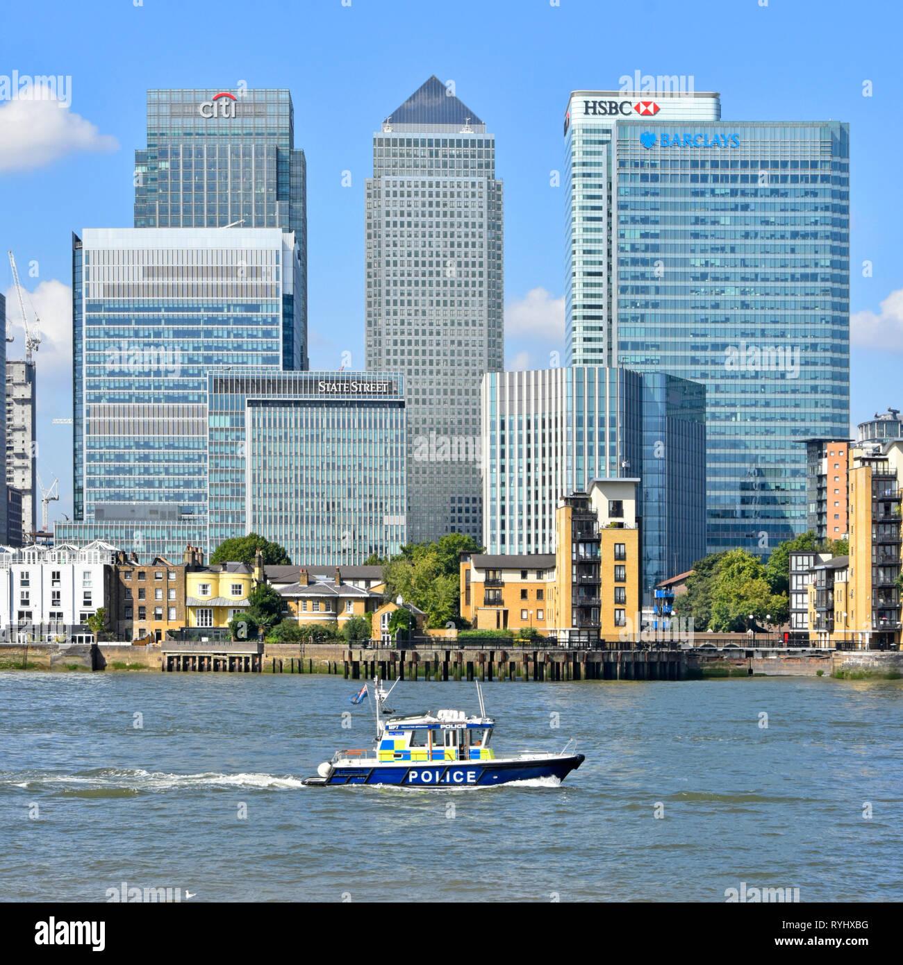 Metropolitan police River Thames patrol passing modern landmark skyscraper building on Canary Wharf Isle of Dogs London Docklands skyline  England UK - Stock Image