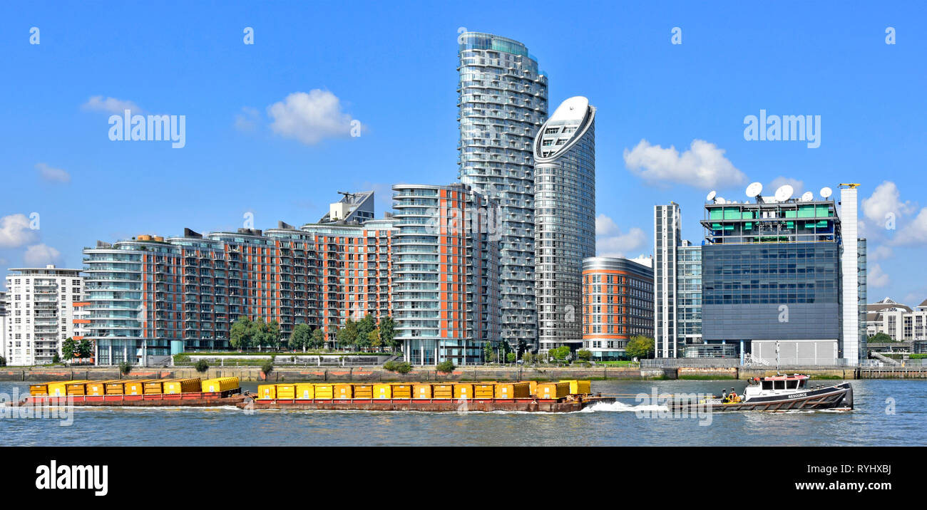 River Thames tug boat & barge containers full of London waste rubbish towed down river for recycling modern apartment building Poplar East London UK - Stock Image