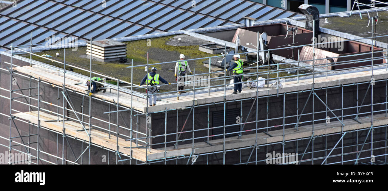 Aerial birds eye view from above London tall office building roof workers erecting access scaffolding for rooftop repairs City of London England UK - Stock Image