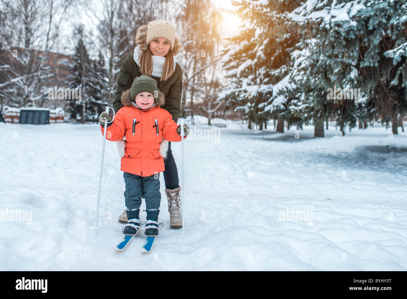 A young woman, mom supports with care, skiing in winter in the forest park, a little son a boy of 3-6 years. The first sports lessons on the street Stock Photo