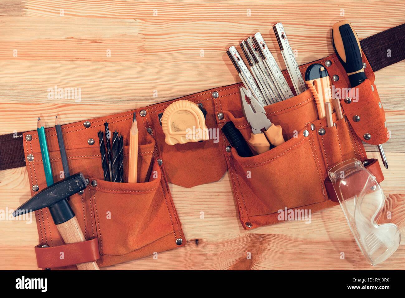 Organized handyman tool belt on work desk Stock Photo
