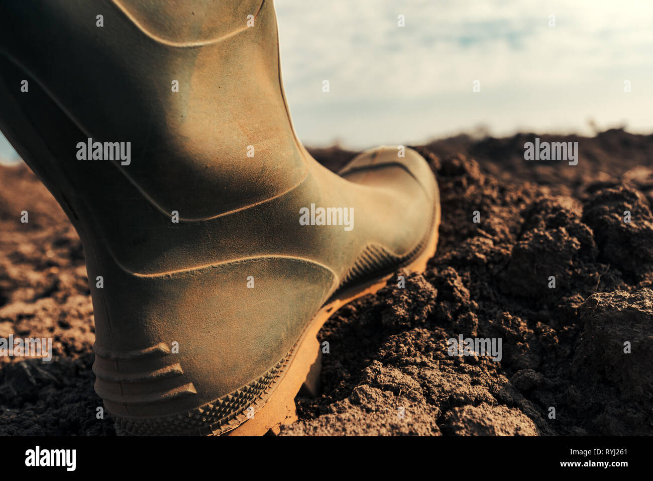 Farmer in wellington rubber boots making first step in field, close up. Beginning of agricultural season and starting of activities on farmland. - Stock Image