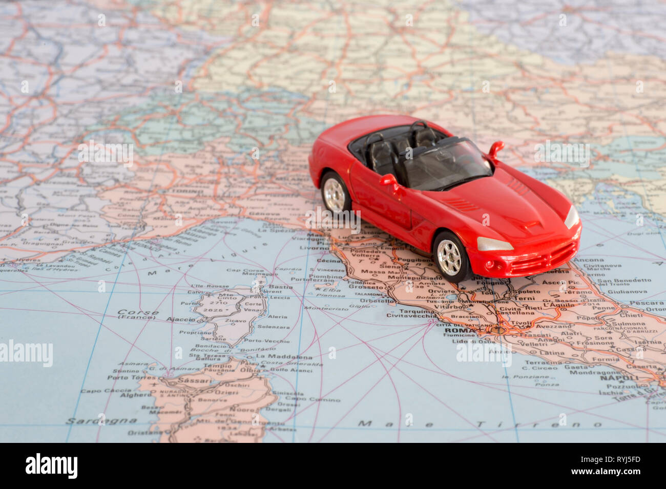 Toy red car on the geographical map of Europe. Travel route planning concept. Stock Photo