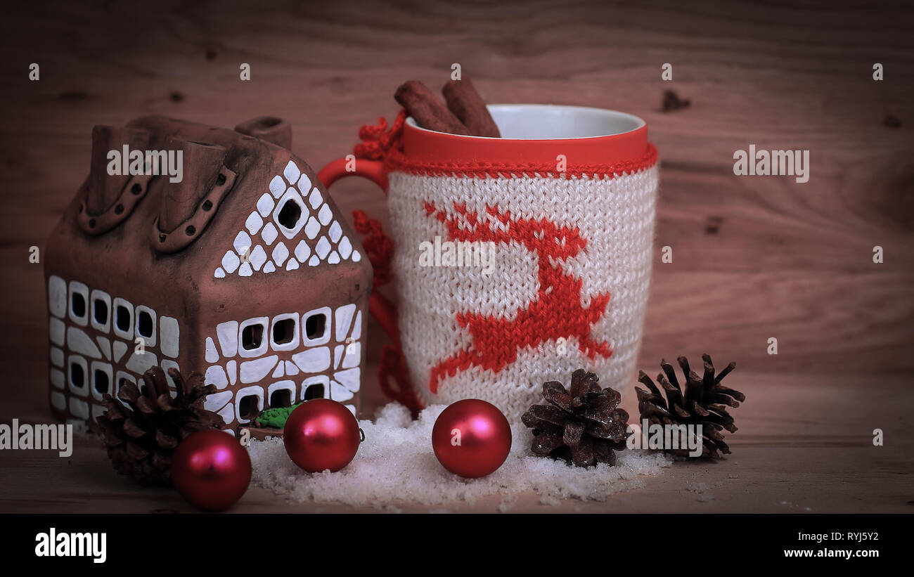 Christmas Cup and a gingerbread house on a wooden table . - Stock Image