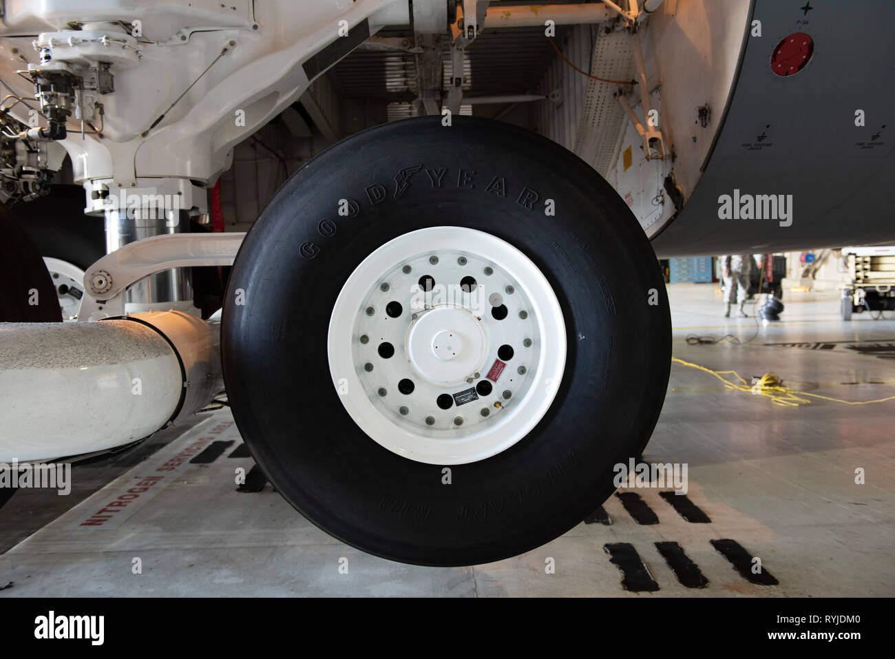 The rear wheel assembly of a C-5M Super Galaxy aircraft is serviced inside a hangar, March 13, 2019 at Travis Air Force Base, California. The C-5M Super Galaxy's high flotation main landing gear provides 28 wheels to distribute gross weight on paved or earth surfaces. The rear main landing gear can be made to caster on an angle to make a smaller turning radius, and rotates 90 degrees after takeoff before being retracted. (U.S. Air Force photo by Heide Couch) - Stock Image