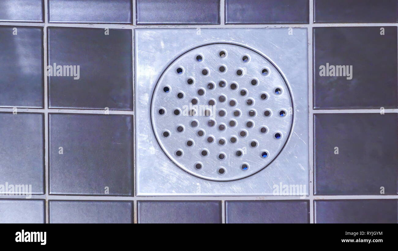 The drainage hole on the floor of the bathroom with the color blue tiles on it - Stock Image