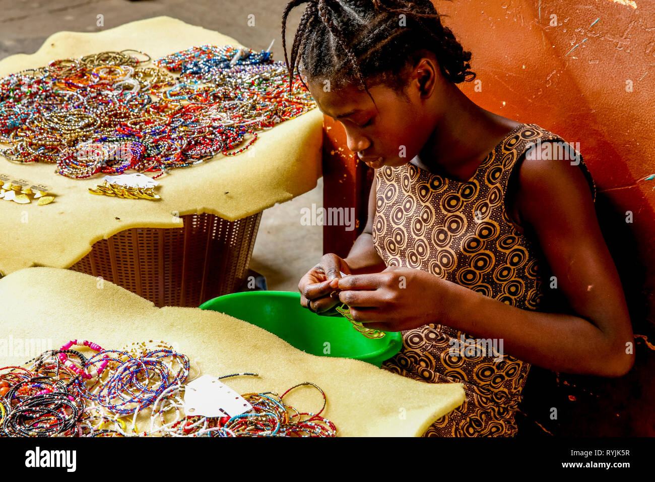 Girl making and selling jewelry in Ouagadougou, Burkina Faso