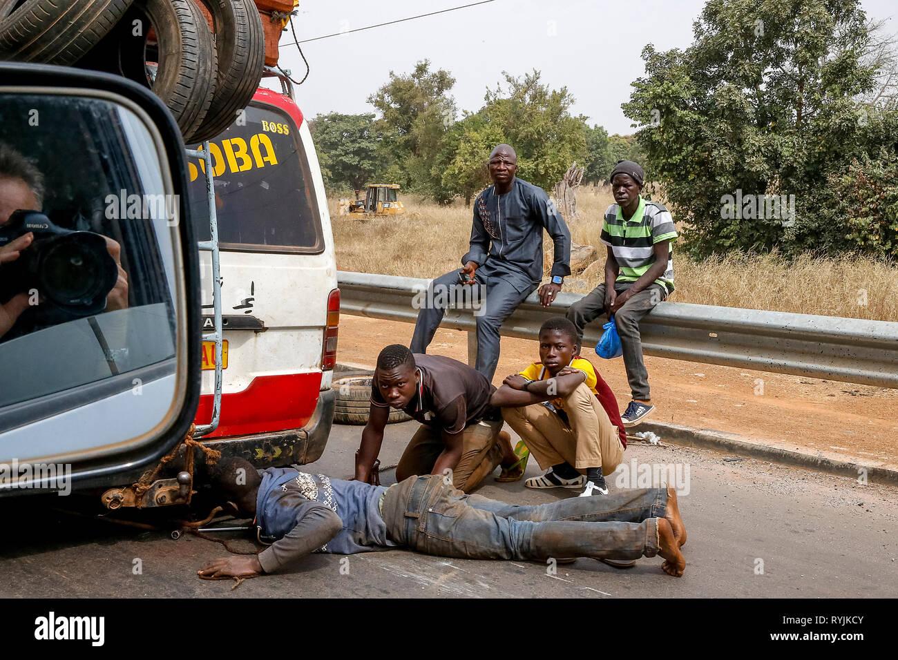 Public transport minibus breakdown on a Burkina Faso road. - Stock Image