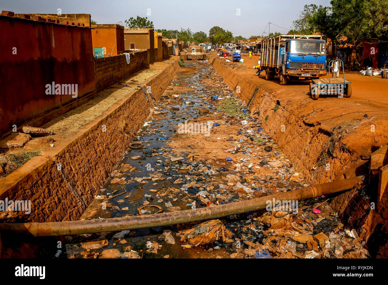 Littered open-air sewer in Ouahigouya, Burkina Faso. - Stock Image