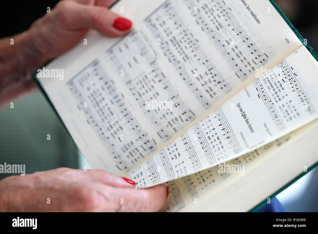 Woman reading Alleluia, a protestant Praise and Worship Songbook. - Stock Image