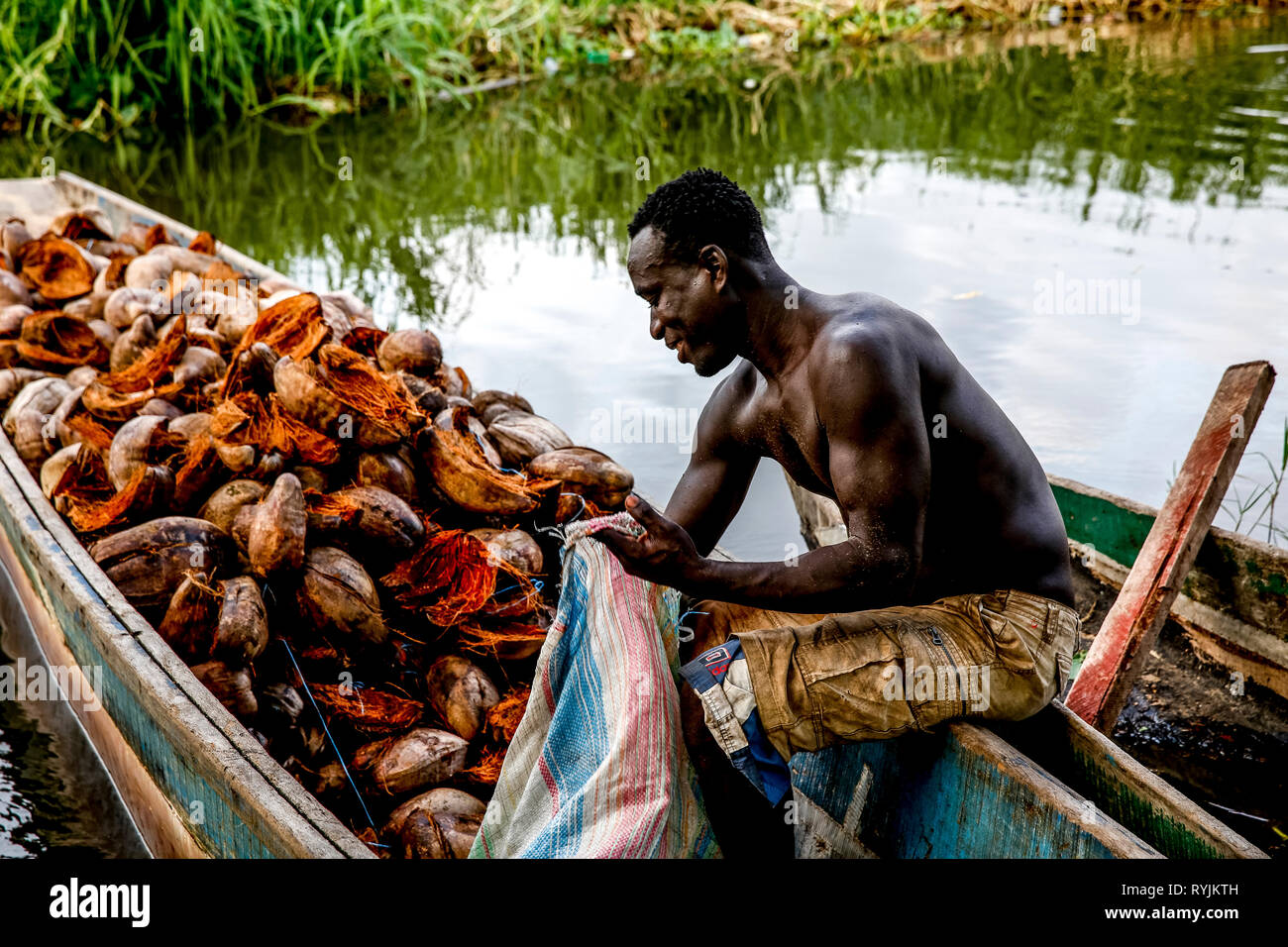 Man filling a bag with coconut husks in a canoe in Grand Bassam, Ivory Coast. - Stock Image
