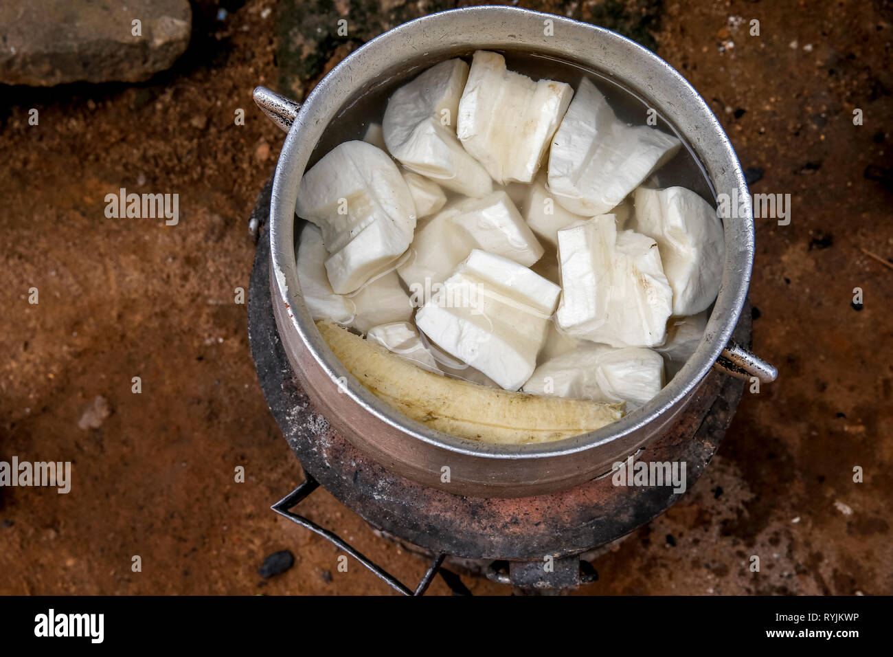 Traditional dish cooking in a village near Agboville, Ivory Coast. Yams mixed with plantain. Stock Photo