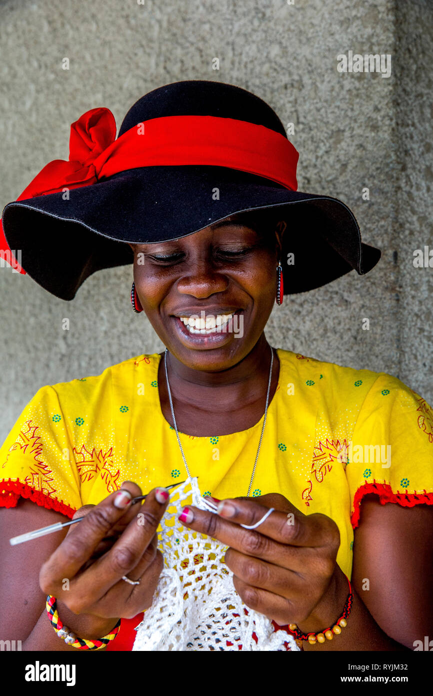 Catholic woman knitting outside Our Lady of Africa sanctuary, Ivory Coast. - Stock Image