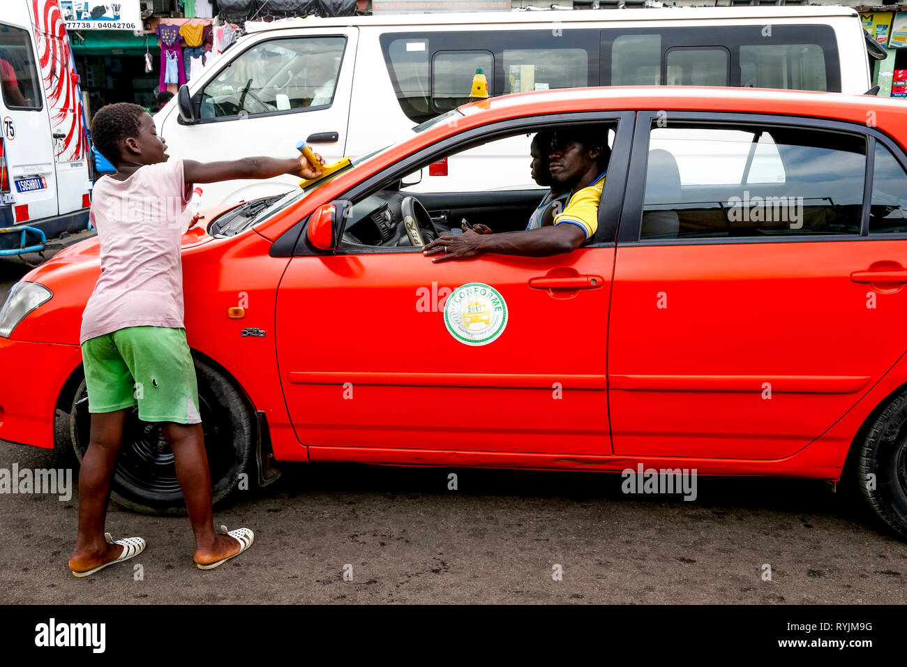 Boy cleaning a car windshield in the traffic in Yopougon, Abidjan, Ivory Coast. - Stock Image