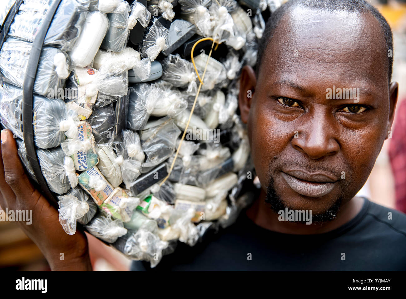 Man carrying cell phones in Abidjan, Ivory Coast. - Stock Image