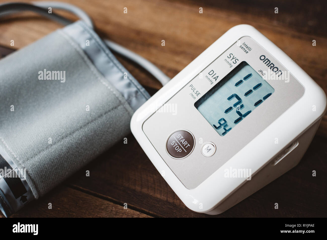 Petaling Jaya, Selangor, Malaysia - 14 March 2019 : Sphygmomanometer or electronic blood pressure from brand OMRON on a wooden desk. Omron is a well k - Stock Image