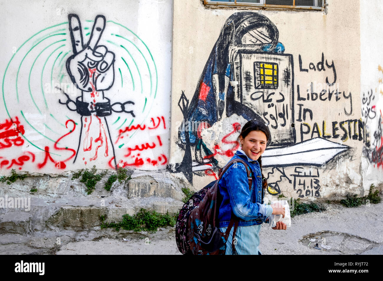Schoolgirl walking past a tagged wall in Jalazone refugee camp near Ramallah, West Bank, Palestine. Stock Photo
