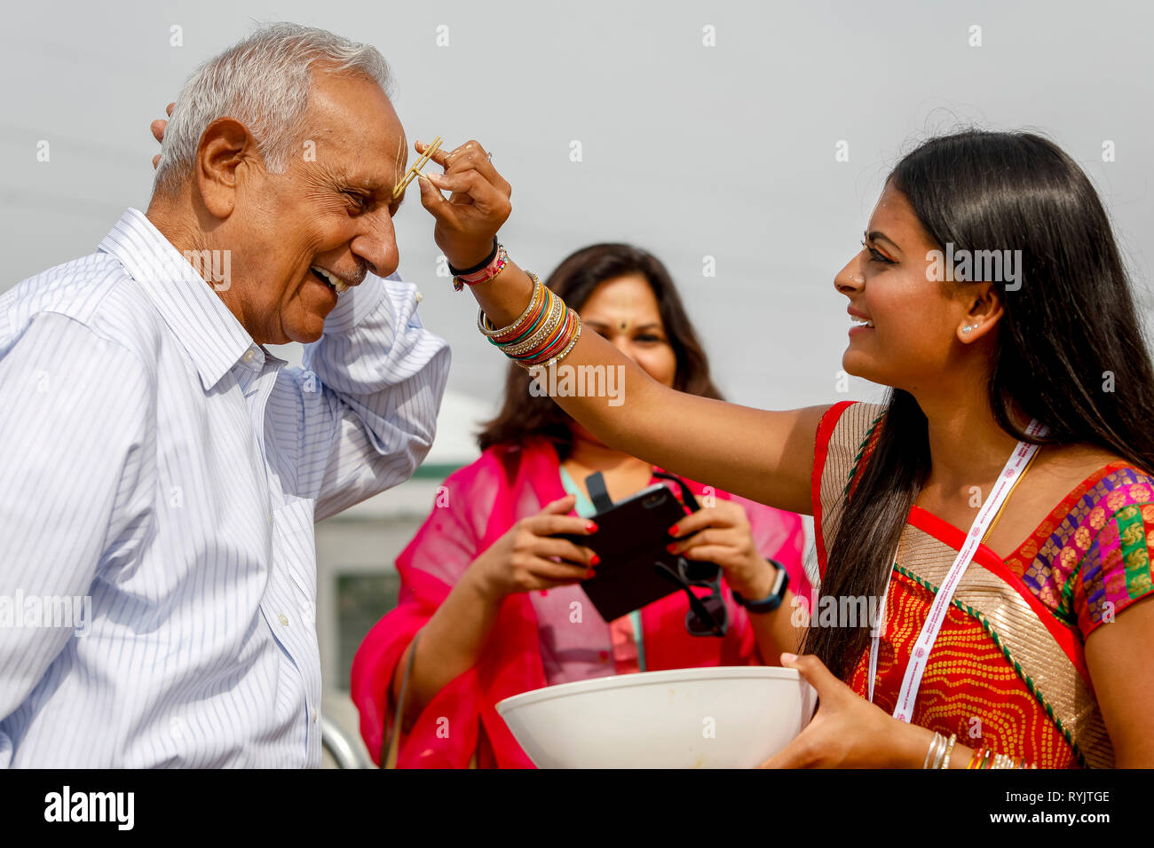 Greeting at Janmashtami hindu festival, Watford, U.K. Guests receive a mark on their forehead. - Stock Image