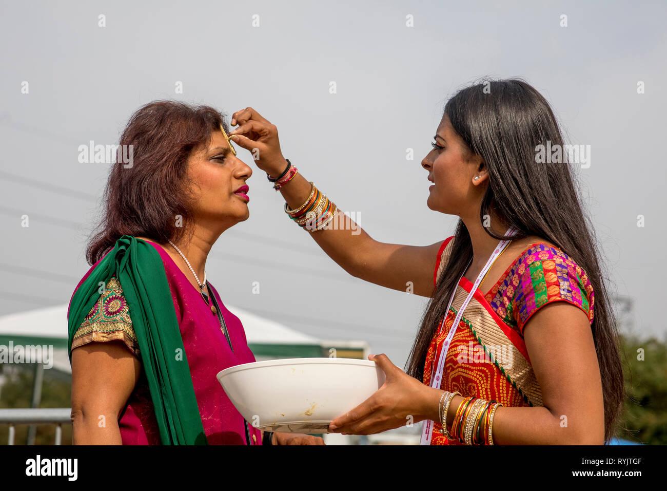 Greeting at Janmashtami hindu festival, Watford, U.K. Guests receive a mark on their forehead. - Stock Image