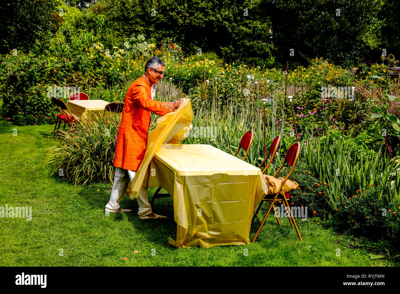 Volunteer laying a table for guests in the flower garden at Bhaktivedanta manor during Janmashtami hindu festival, Watford, U.K. - Stock Image