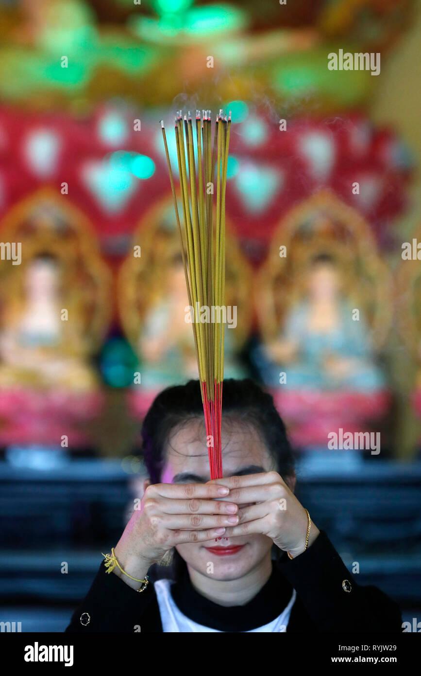 Huynh Dao buddhist pagoda  Woman praying the Buddha  Incense