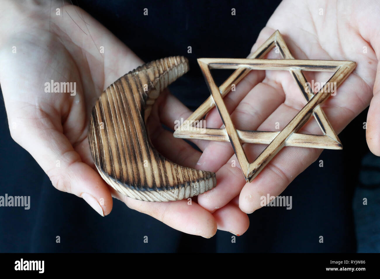 Islam and Judaism.  Jewish  Star of David and muslim Crescent :  Interreligious symbols in hands. Stock Photo