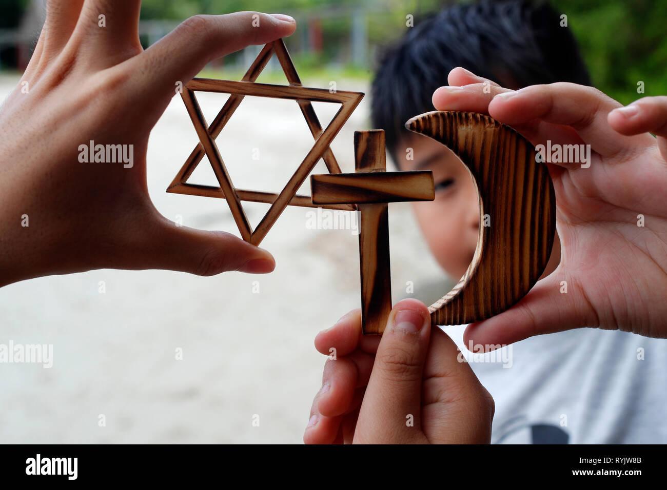 Christianity, Islam, Judaism  3  monotheistic religions. Jewish  Star, Cross and Crescent :  Interreligious symbols in hands. - Stock Image
