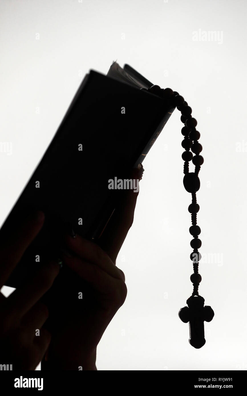 Silhouette of a christian woman reading the bible with